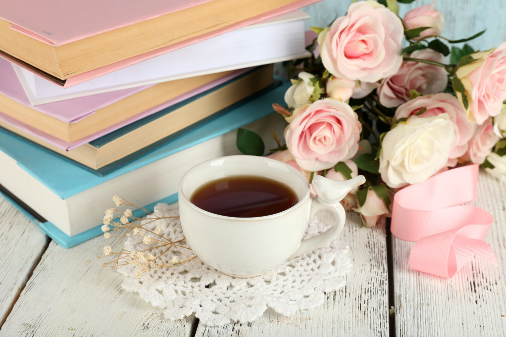 Cup of tea with books and flowers on wooden background